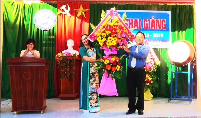 Đồng chí Bùi Võ Quảng - Phó Bí Thư, Chủ tịch HĐND huyện tặng hoa chúc mừng trường THCS Lê Quý Đôn (Ảnh Quốc Vương)